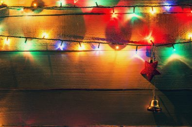 Christmas lights and globes on wood background